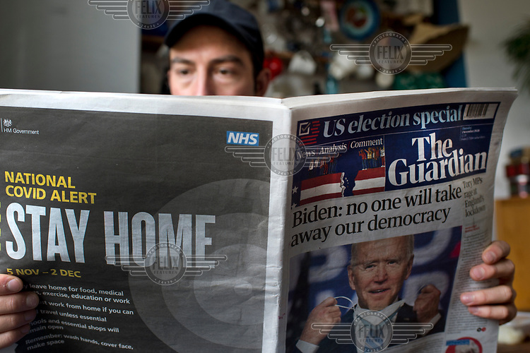 A young man reads The Guardian of 5 November 2020 with a back page advert by the Government, annoucing the lockdown due to run from 5/11/2020 - 02/12/2020.