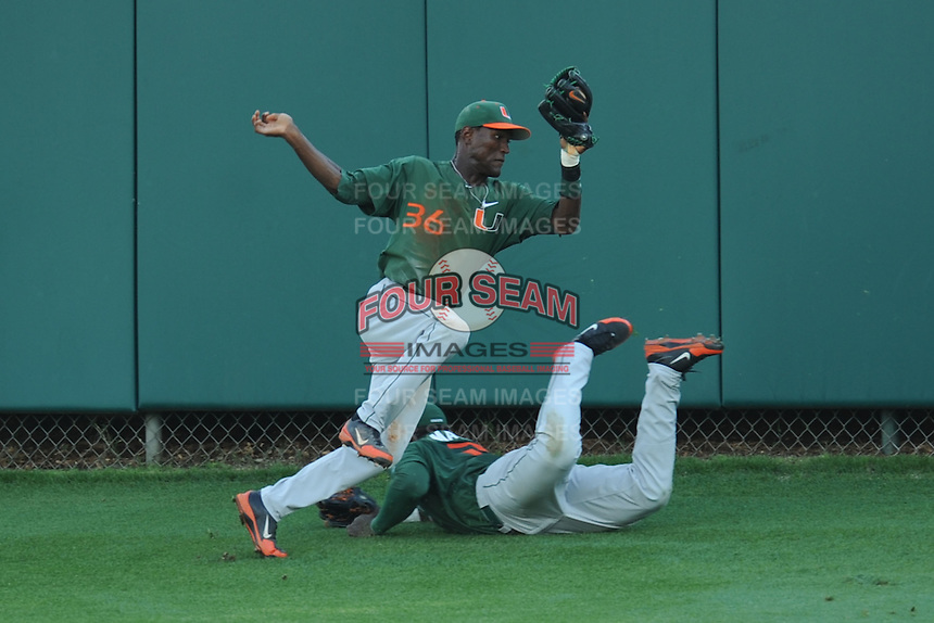 Center Fielder Dale Carey #36 makes a diving catch over a sliding right fielder Chantz Mack #2 during a  game against the Clemson Tigers at Doug Kingsmore Stadium on March 31, 2012 in Clemson, South Carolina. The Tigers won the game 3-1. (Tony Farlow/Four Seam Images).