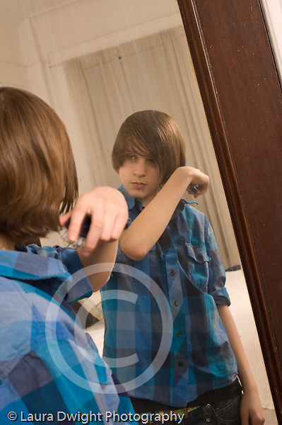 Teenage boy looking at self in mirror brushing combing or adjusting hair Caucasian vertical age 14