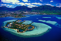 Aerial view of University of Hawaii's Coconut Island Marine laboratory and Kaneohe Bay and with it's many table reefs and sand bars. Koolau Mountains in background