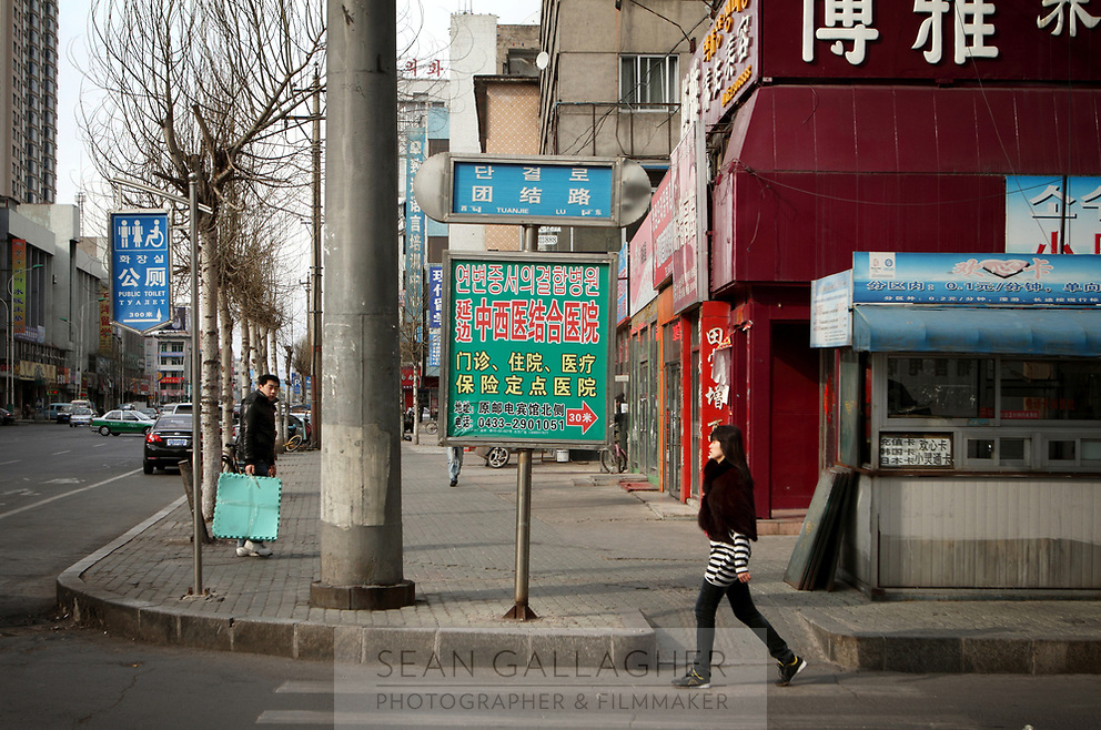 China. Jilin Province. Pedestrians  in the town of Yanji, close to the border with North Korea. The town is part of the Korean Autonomous Prefecture, hence many signs are in both Chinese and Korean. 2011