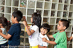 Preschool 3-5 year olds  group of children boy and girls holding each other's shoulders in a line circle time activity laughing boy shorter than his peers horizontal New York City