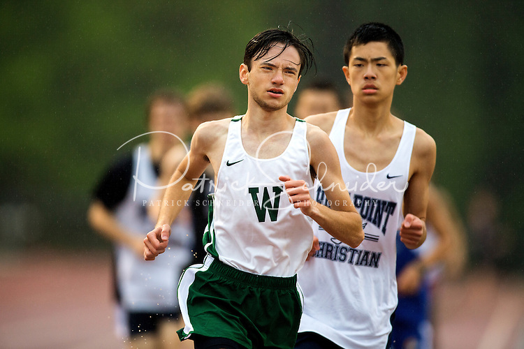 Sports action photography of the Woodlawn School track team in action at their rainy meet at Cannon School in Concord, NC.<br /> <br /> Charlotte Photographer - PatrickSchneiderPhoto.com