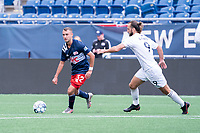 FOXBOROUGH, MA - JULY 4: Marios Lomis #9 of Greenville Triumph SC comes in to pressure Jake Rozhansky #32 of the New England Revolution II during a game between Greenville Triumph SC and New England Revolution II at Gillette Stadium on July 4, 2021 in Foxborough, Massachusetts.