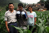 Miao Yun Fei, 16, with his parents, in their farmhouse in Honggi Village in the mountains of Sichuan Province, China. The group of young boxers are hoping to make it to become some of China's first professional boxers...PHOTO BY SINOPIX