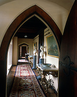 A gothic doorway opens onto a long corridor furnished with antique console tables and a pair of busts displayed on blue marble plinths