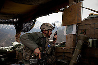 US Army Soldier Sgt. Baker from Viper Company 126, 1st Platoon, directs artillery after being hit by 10 RPGs at Restrepo Firebase in the restive Korengal Valley. They are usually attacked daily with small arms fire but 10 RPGs were launched at them in this firefight, five of which hit the base perimeter. Restrepo, a remote outpost, is known as one of the most violent places in Afghanistan. Located in the Korengal Valley it comes under fire on a daily basis from Anti-Afghan Forces in the local villages and mountains.