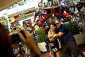 A couple poses for a photo with a giant robot at a toy-show in a mall in Manila in Philippines. Photo: Sanjit Das