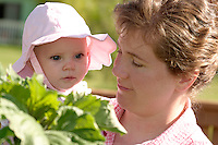 Woman holding baby girl in garden on summer day