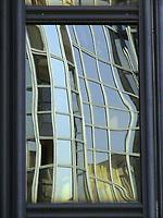 The twisted reflected image of a window that is divided in rectangles by white frames. Across the reflected glass one can distinguish the books of a bookcase (Paris, 2007).<br /> <br /> L'immagine riflessa distorta di una vetrata divisa in rettangoli da cornici bianche. Attraverso il vetro riflesso si possono distinguere i libri di una libreria (Parigi, 2007).