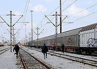Pictured: Migrant men run to climb onto a moving freight train at the OSE depot in Thessaloniki, Greece. Wednesday 05 April 2017<br /> Re: A year after an agreement was signed between Greece and Turkey for the management of refugees. Migrants, mostly from Morocco, Algeria and Tunisia, have been living in disused train carriages at the Thessaloniki freight depot of OSE in northern Greece, the company managing the railways in the country. Some of the migrants climb onto moving trains, or even hide themselves in storage areas, hoping that they will cross the border.