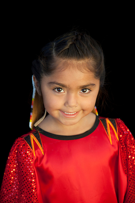 Young girl and pow wow dancer, Lyric Dixey (Shoshone-Bannock), smiles as she hows off her pretty red dress during the Fort Hall Indian Festival.