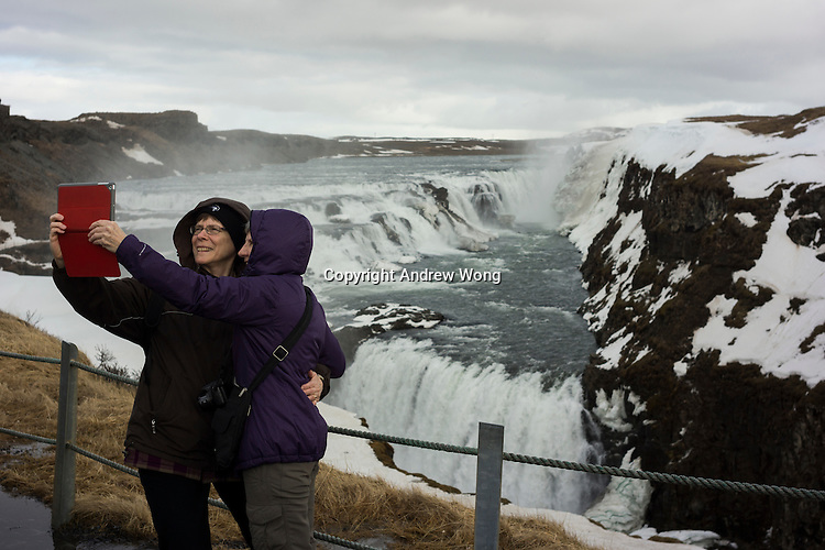 Gullfoss, Iceland - Tourists pose for selfies at Gullfoss waterfall, which is one of the most popular tourist attractions in Iceland, March 2016.