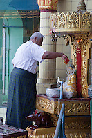 Myanmar, Burma, Yangon.  Sule Pagoda.  Worshiper Pouring Water over Small Buddha Statue.  The man is wearing a longyi, or bahso, the traditional wrap-around sarong covering the legs.
