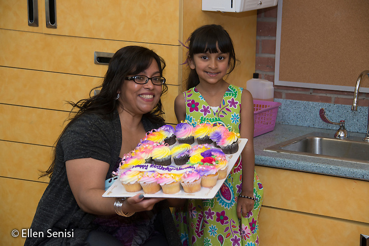 MR / Schenectady, NY. Zoller Elementary School (urban public school). Kindergarten classroom. Portrait of mother (Caribbean American) bringing her daughter (6, biracial) cupcakes to celebrate her six year old birthday in the classroom. MR: Myk2, Myk1. ID: AM-gKw. © Ellen B. Senisi.