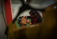 A make up artist takes care of Ali Saleem's eye lashes and eye lids.