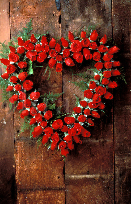 Red rose heart shaped wreath on a weathered wooden door..