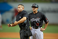 Birmingham Barons manager Omar Vizquel (13) talks with umpire Jonathan Parra during a Southern League game against the Chattanooga Lookouts on May 2, 2019 at Regions Field in Birmingham, Alabama.  Birmingham defeated Chattanooga 4-2.  (Mike Janes/Four Seam Images)