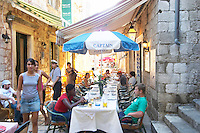 View along the Prijeko street with restaurants with outside seating long tables and chairs lining the street under sun shades. The Captain restaurant with some tourists having dinner and two young girls walking past. Dubrovnik, old city. Dalmatian Coast, Croatia, Europe.