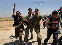 """Palestinian carrying an injuerd child during  Hamas demonstration in the Karni crossing east of Gaza City that injured 10 people and killing people by the Israeli army on ,May 22, 2008 """"photo by Thair alhassany"""""""