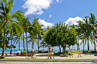 People enjoy a walk or bike ride along the palm tree lined and historic Kalakau Avenue that parallels beautiful Waikiki Beach,Oahu.