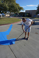 Mission Bay High School, San Diego CA, USA.  Saturday, October 10th 2015:  Mission Bay High School principal, Ernie Remillard paints a blue wave as part of a  street mural in front of the High School Gym.  The mural installation was funded by the non-profit organization Beautiful PB throgh a grant from SANDAG.