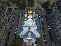 """Switzerland. Geneva. Aerial photography. The picture on the Russian Church is shot from an elevated/direct-down position by an unmanned aerial vehicle (UAV), commonly known as a drone.The Russian Church (full name: Cathédrale de l'Exaltation de la Sainte Croix) is designed in a Byzantine Moscovite style. The church is a lovely 19th-century Russian Orthodox church topped with golden onion domes. The church, facade. roof and all onion domes underwent a complete revival restoration. The newly restored bulbs are gilded with golden leaves. The term gilding covers a number of decorative techniques for applying fine gold leaf to solid surfaces such as onion domes and crosses. A gilded object is also described as """"gilt"""". The Russian church serves today not only the Russian community but also Bulgarians, Serbs, Coptic Christians and other Orthodox worshippers who do not have their own church in Geneva. An onion dome is a dome whose shape resembles an onion. Such domes are often larger in diameter than the drum upon which they sit, and their height usually exceeds their width. These bulbous structures taper smoothly to a point. Drone Pilot Stefan Hess. 10.08.2017 © 2017 Didier Ruef"""