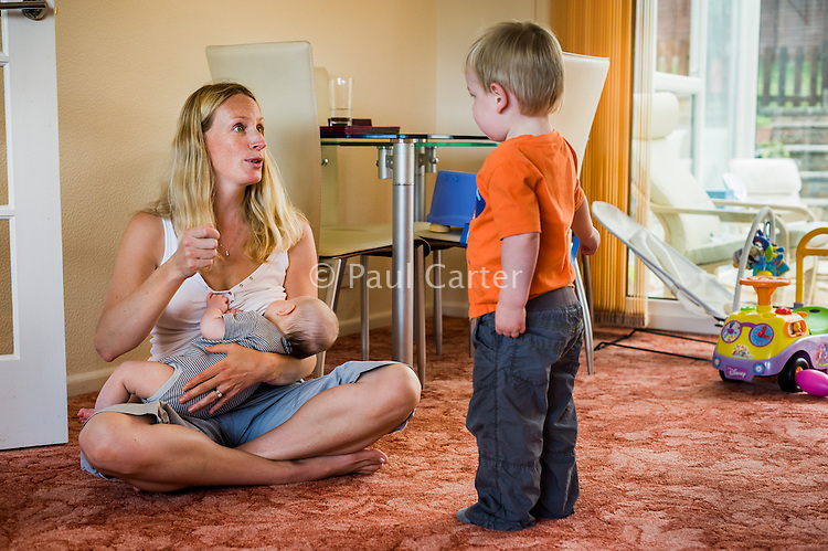 A woman sitting crossed-legged at home on her living room carpet, talking to her toddler son and  breastfeeding her baby.<br /> <br /> 09/07/2011<br /> Hampshire, England, UK