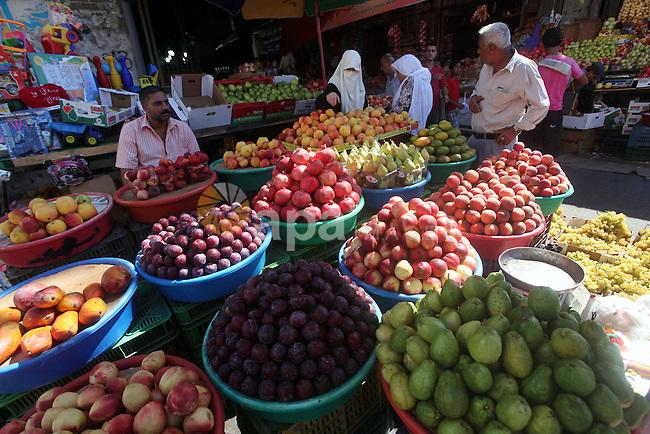 A Palestinian vendor displays fruits at a market in Gaza | apaimages