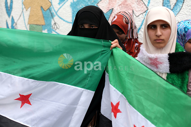 Palestinian women hold Syrian revolution flag during a demonstration in support of the Syrian people in front of U.N. headquarter office in Gaza city on February 5, 2013. Pressure mounted on Syrian President Bashar al-Assad to respond to a surprise offer of talks by his main political opponents aimed at ending warfare in which tens of thousands of people have died. Photo by Majdi Fathi