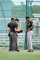 FCL Pirates Black pitcher Cristopher Cruz (30) jokes with umpires Alex Lawrie and Matt Wotkoski while getting checked for a foreign substance during a game against the FCL Pirates Gold on July 2, 2021 at Pirate City in Bradenton, Florida.  (Mike Janes/Four Seam Images)