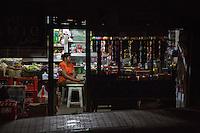 Bali, Indonesia.  Shopkeeper at Night.  Klungkung, Semarapura.