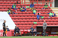 Reading Manager, Mark Bowen, watches on from the touchline as the Reading substitutes observe the social distancing guidelines by sitting two metres apart in the stand during Charlton Athletic vs Reading, Sky Bet EFL Championship Football at The Valley on 11th July 2020