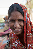 Rajasthan, India. Sawai Madhopur. Smiling local tribal woman with pierced nose and Hindu bindi religious mark on her forehead.