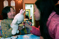 11 year old Liu Fangyuan (Yuan Yuan) plays with a neighborhood friend 10 year old Wang Yin in the bedroom that she shares with her parents in Nanjing, China. In 2002, Yuan Yuan's aunt poured sulfuric acid on her face after losing a housing dispute with Yuan Yuan's father. The attack blinded and seriously disfigured Yuan Yuan, while her aunt is serving a life sentence in prison, Yuan Yuan and her family awaits a controversial face transplant...PHOTO BY SHEN / SINOPIX