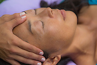 A woman relaxes while receiving a facial massage at an outdoor location on O'ahu.