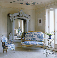 The outsize mirror in this living room is integral to the wall and the plaster mouldings and furniture were inspired by 18th century France