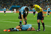 Alvaro Pereira of Uruguay is unconscious as the referee and Diego Godin check on him