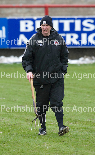 Brechin v St Johnstone....12.03.11  Scottish Cup Quarter Final.Kevin McGowne out on the Glebe Park pitch before kick off, forking in an attempt to drain the surface water.Picture by Graeme Hart..Copyright Perthshire Picture Agency.Tel: 01738 623350  Mobile: 07990 594431