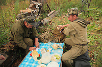 Sabit Galin and Aglam Ramujin, forest wardens, around a makeshift table in the camp.