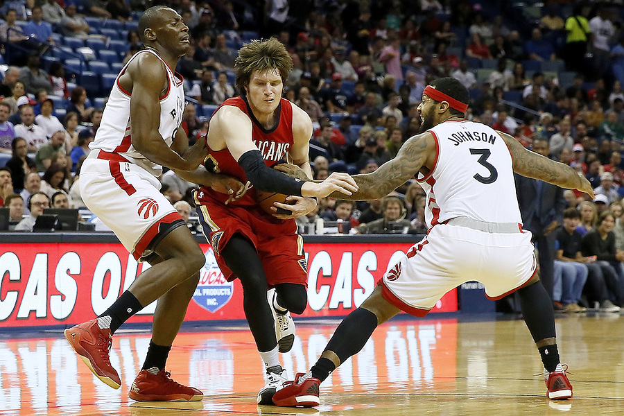 NEW ORLEANS, LA - MARCH 26: Luke Babbitt #8 of the New Orleans Pelicans drives between Bismack Biyombo #8 of the Toronto Raptors and James Johnson #3 of the Toronto Raptors during the first half of a game at the Smoothie King Center on March 26, 2016 in New Orleans, Louisiana. NOTE TO USER: User expressly acknowledges and agrees that, by downloading and or using this photograph, User is consenting to the terms and conditions of the Getty Images License Agreement.  (Photo by Jonathan Bachman/Getty Images)