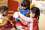 Educaton preschool  3-4 year olds water table with soap bubbles three girls playing one watching the other two pour some water height difference same age but one girl shorter than the other two horizontal