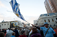 A Uruguay fan waves a flag while Fans crowd the Cape Town fan walk before the 2010 FIFA World Cup semi-final between the Netherlands and Uruguay at Greenpoint Stadium in Cape Town, South Africa on Tuesday, July 6, 2010.  Netherlands defeated Uruguay 3-2.