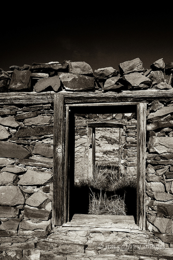 A sepia toned image looking into a roofless abandoned stone house through a window and out through a door on the opposite side
