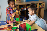 Education Preschool 2-3 year olds two girls building magnet tile structures and playing with dolls