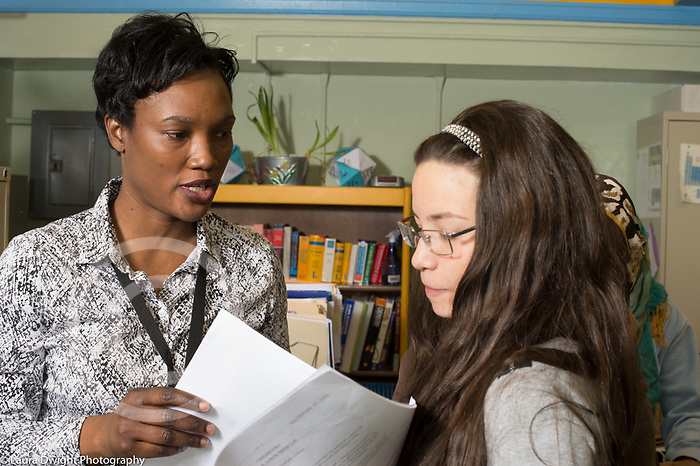 Education High School biology teacher talking to female student about her work