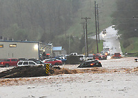 Flood water surges Wednesday April 28 2021 across Dream Valley Road on the east edge of Rogers, about 100 yards south of Arkansas 12. Go to nwaonline.com/210429Daily/ to see more photos.<br />