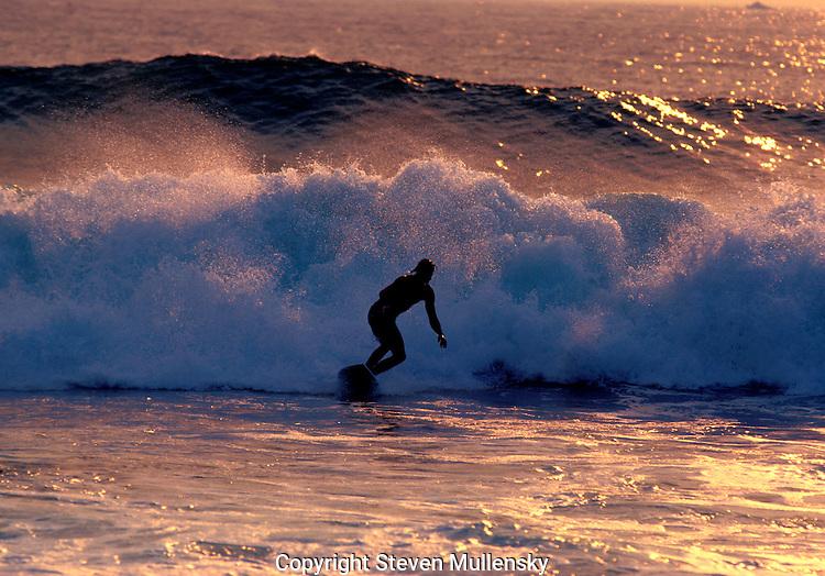 A California surfer rides the foam of a crashing wave.