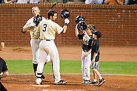 Carlos Lopez #3 of the Wake Forest Demon Deacons is congratulated at home plate by teammate Charlie Morgan #26 and 2 bat boys after hitting a solo home run against the Miami Hurricanes at NewBridge Bank Park on May 25, 2012 in Winston-Salem, North Carolina.  The Hurricanes defeated the Demon Deacons 6-3.  (Brian Westerholt/Four Seam Images)