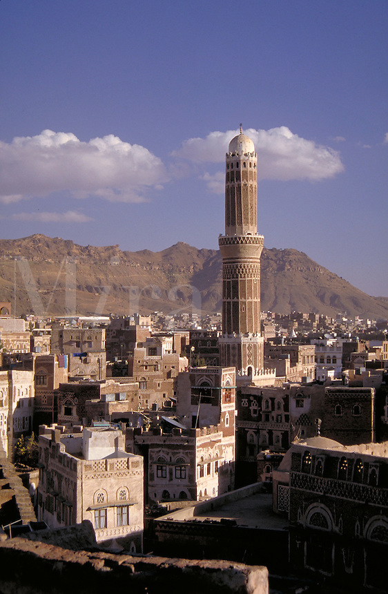 Tall, domed minaret tower projecting high above Sana's rooftops. Architecture, mosque, religion, cityscapes, moutains rise as a backdrop, Islam. Sana, Yemen.